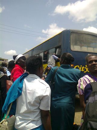 students enter a matatu through the window.